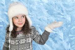 Little girl keeps aside her hand in a mitten on winter background Royalty Free Stock Photography
