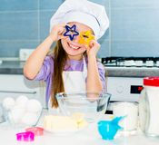 Little girl and keeps cookie cutters Stock Images