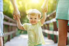 Little girl keeps for hands of parents in park Stock Images