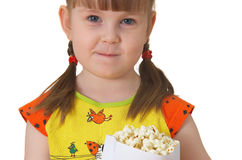 Little girl keeps package with popcorn. Little girl sits on chair, smiles and keeps package with popcorn Stock Image