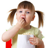 Little girl keeps package with popcorn. Little girl sits on chair, keeps package with popcorn and eats Stock Images