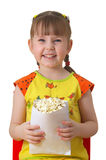 Little girl keeps package with popcorn. Little girl sits on chair, smiles and keeps package with popcorn Stock Photography