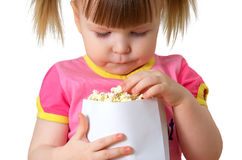 Little girl keeps package with popcorn. Little girl sits on chair, smiles and keeps package with popcorn Royalty Free Stock Photos