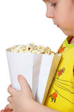Little girl keeps package with popcorn. Little girl sits on chair and keeps package with popcorn Stock Photos