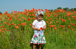 The little girl keeps red poppy in a poppy field Royalty Free Stock Photos