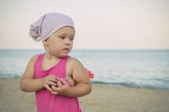 Little girl in kerchief on the sea in summer stock photography