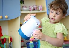 Little girl with kettle and cup in hands Stock Photography