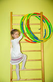 Little girl kid climbs the stairs on sports equipment in kindergarten. Wall bars. Children`s sports. Healthy lifestyle from childh Royalty Free Stock Images