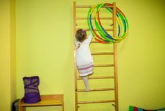 Little girl kid climbs the stairs on sports equipment in kindergarten. Wall bars. Children`s sports. Healthy lifestyle from childh Royalty Free Stock Photos