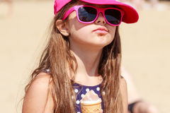 Little girl kid eating ice cream on beach. Summer. Royalty Free Stock Images