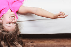 Little girl kid with long hair upside down on sofa Royalty Free Stock Images
