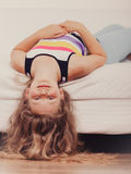 Little girl kid with long hair upside down on sofa Stock Images