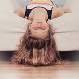 Little girl kid with long hair upside down on sofa. Little girl with long hair lying upside down on sofa at home. Kid playing having fun on couch Stock Photos