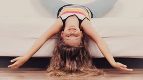 Little girl kid with long hair upside down on sofa Stock Photos