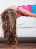 Little girl kid with long hair upside down on sofa. Little girl with long hair lying upside down on sofa at home. Kid playing having fun on couch Stock Photo