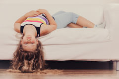 Little girl kid with long hair upside down on sofa. Little girl with long hair lying upside down on sofa at home. Kid playing having fun on couch Royalty Free Stock Photography