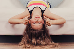 Little girl kid with long hair upside down on sofa Stock Image
