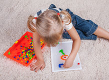 Little girl kid playing with education mosaic pins Royalty Free Stock Photo