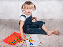 Little girl kid playing with education mosaic pins Royalty Free Stock Image