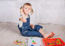 Little girl kid playing with education mosaic pins Stock Images