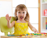 Little girl kid playing with logical toys. Child sorting and arranging colors and forms. Royalty Free Stock Image