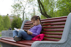 Little girl kid reading a book sitting on a bench. In spring park Stock Photos