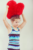 Little girl kid with red heart shape pillow. Stock Images