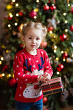 Little girl kid in the red sweater holding a gift on new year ba Stock Photo