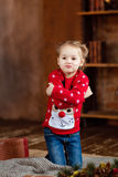Little girl kid in the red sweater makes faces at Christmas back Stock Photography