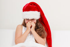 Little girl kid in santa hat giggling. Christmas. Cute little girl kid in red santa claus hat and white dress giggling. Chrtistmas holiday season Stock Photo