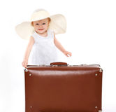 Little girl kid in a straw summer hat and with suitcase Royalty Free Stock Images