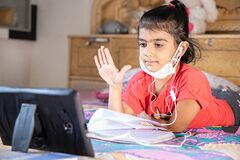 Little girl kid student raise her hand while studying online class with tablet at home, New normal.Covid-19 coronavirus.Social