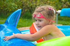 Little girl, kid, swimming in the pool, inflatable circles, afraid, sunny stock image