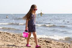 Little girl kid walking on beach at sea. Fun. Stock Images