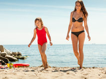 Little girl kid and woman mother on beach. Royalty Free Stock Images