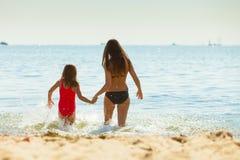 Little girl kid and woman mother in sea water. Fun Stock Image