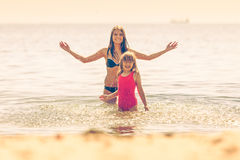 Little girl kid and woman mother in sea water. Fun Stock Photo