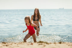 Little girl kid and woman mother in sea water. Fun Royalty Free Stock Images