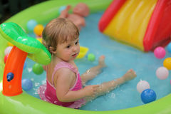 Little girl in kids pool. Cute little girl having fun in the inflatable kids pool in the garden Stock Photos