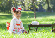 The little girl in kimono sitting on the grass Stock Images