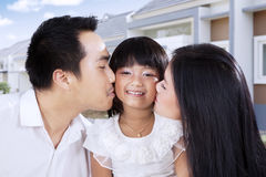 Little girl kissed by her parents Royalty Free Stock Photos