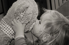Little girl kisses bear toy for good-bye. Little caucasian girl kisses soft bear toy good-night. Closeup Royalty Free Stock Photography