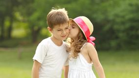 Little girl kisses the boy on the cheek, he is embarrassed and smiles. Slow motion. Children hold hands, the little girl kisses the boy on the cheek, he is stock video footage
