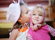 Little girl kisses sister. Royalty Free Stock Image