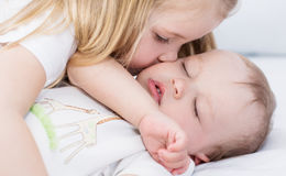 Little girl kisses a sleeping baby brother. On a white background Royalty Free Stock Photography