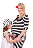 Little girl kissing belly of pregnant mother. On white Royalty Free Stock Images