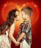 Little girl kissing boy. Littlt girl kisses a boy and holding his hands. Love concept Royalty Free Stock Image