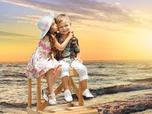 Little girl kissing boy on sea landscape at sunset. Girl embraces and kisses a boy Stock Photography