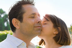 Little Girl Kissing Dad on Cheek. A Special Father Daughter Moment of Affection Stock Photos