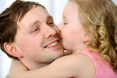 Little girl kissing fathers cheek Stock Photos